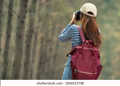 A woman photographer traveler trip on nature park with vintage camera during morning time