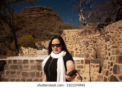 Woman photographer working on photographic shots using a trigger gun in an archaeological zone dating from 1153 in vestiges of the pyramid buried in the chasm of the great hill of the speaker  Mexico