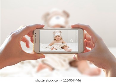 Woman photographing her baby with a cell phone. Photo camera of a smartphone.