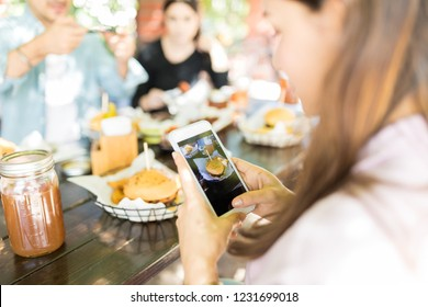 Woman photographing tempting burger on smartphone to upload on social media