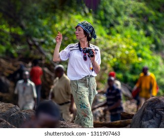 A woman photographs a destructive debris flow destroyed a road between national parks Manyara and Ngorongoro. Car traffic was restored on the same day, Tanzania, East Africa