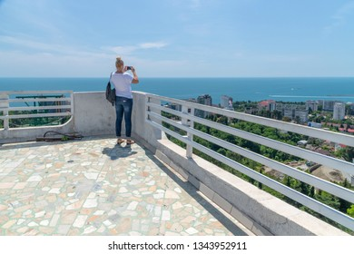 woman photographs on smartphone from viewing platform in Sochi. Russia