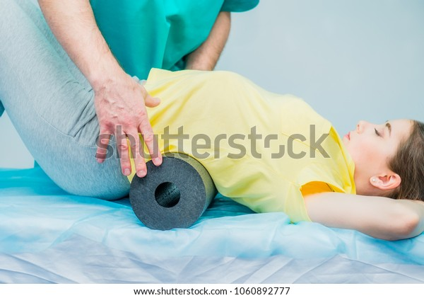 Woman at the physiotherapy doing physical exercises with her therapist, they using a massage roll. A chiropractor treats patient's loins spine in medical office. Neurology, Osteopathy, chiropractic