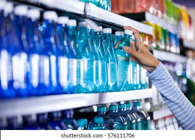 Woman picking bottle of water in grocery section of supermarket