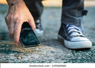 Woman picking up broken smartphone from the ground. Damaged mobile phone with cracked touch screen.
