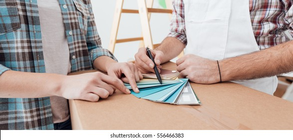 Woman picking a color for her house walls, a professional painter and decorator is showing her color swatches