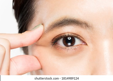 A woman is picking the corner of her eye.