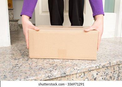 woman picking up the delivering a package from the entrance of her home