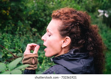 Woman picking and eating wild black berries from a bush
