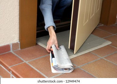 Woman picking up morning paper through the open door