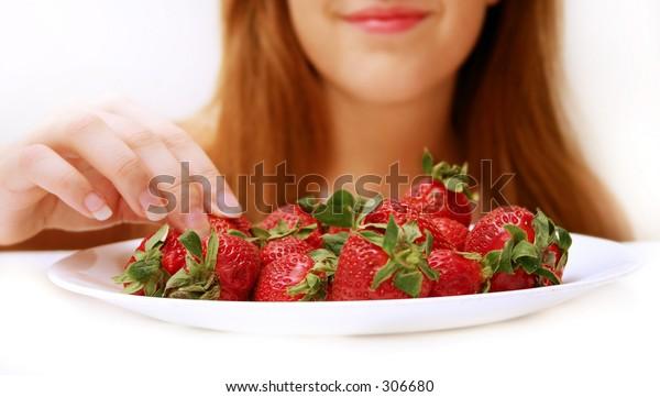 Woman picking a strawberry