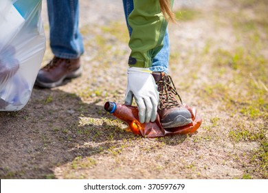 Woman picking up trash. closeup focus on hand