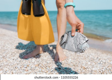 Woman picking up trash in the sea. Woman swimmer cleaning beach from trash. sport and enviromnent concept