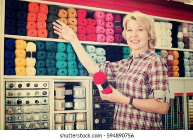 Woman picking yarn and wool balls for hobby in craft shop