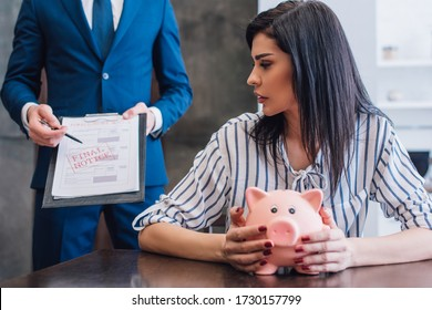 Woman with piggy bank at table near collector pointing with pen at documents with final notice lettering in room