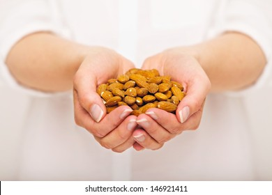 Woman with a pile of crunchy almonds in her hands