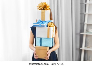 Woman with pile of presents at home