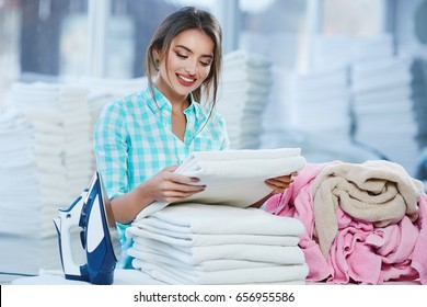Woman piling white linen into heap and smiling. Woman standing near ironing board, heaps of white linen behind. Looking at fresh linen