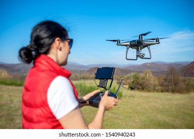 A woman is piloting a drone driving it from a remote control.