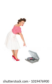 woman in pin up style clothing pointing at phonograph isolated on white