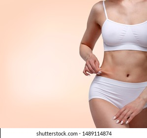 Woman pinches fat on her belly, closeup shot