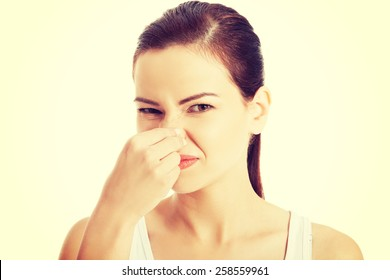 Woman pinches her nose to block a bad smell.