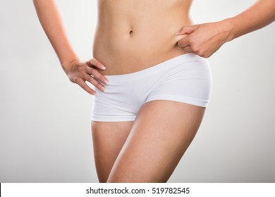 Woman Pinching Excessive Stomach Fat Isolated On Grey Background
