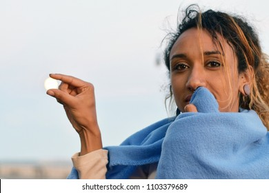 Woman pinching her fingers together as if holding the moon