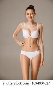 Frauen, die die Haut auf ihrem Bauch kleben und die Fettschicht des Unterhautzellgewebes kontrollieren