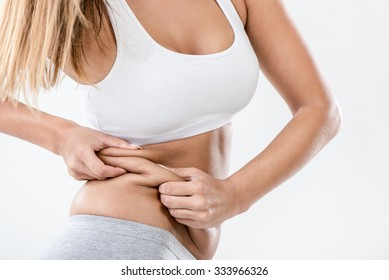 Woman pinching waist and checking her body fat. Close-up.