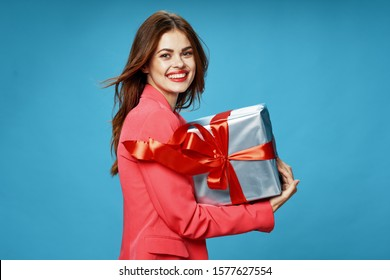 A woman in a pink coat holds a gift box in her hands