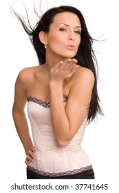 woman in pink corset blowing a kiss isolated on white