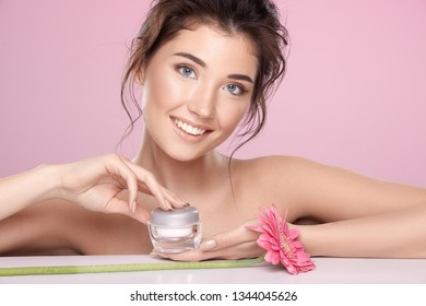 Woman with pink flower and naked shoulders wearing nude make up with perfect skin at pink studio background posing with cream.