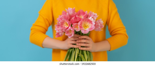 Woman with pink flowers tulips in hands on blue wall background.