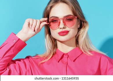 woman in pink glasses on a blue background beauty