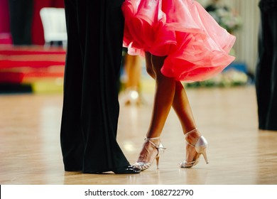 woman in pink gown and man black tailcoat latino dancing