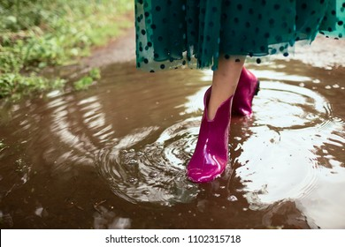 Woman in pink gumboots walks on the pool after rain