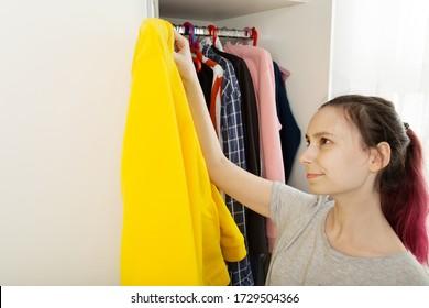 Frau mit rosa Haar wählt Kleidung im Schrank aus und holt gelbe Hoody heraus, schaut sie mit Lächeln an