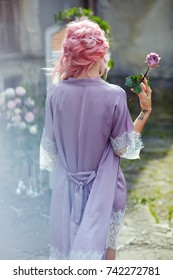 Woman with pink hair walks in violet silk robe with rose in her arms