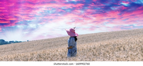Woman with pink hat in a wheat field.
