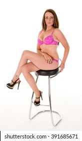 Woman in pink lingerie sitting on bar stool