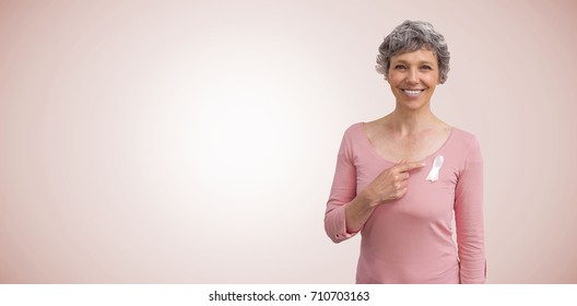 Woman in pink outfits showing ribbon for breast cancer awareness against neutral background