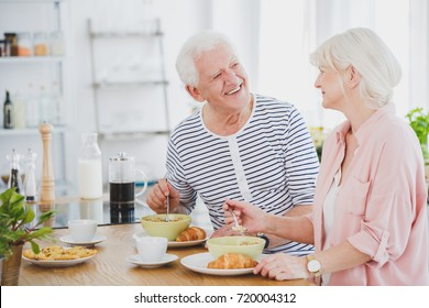 Woman in pink shirt is eating milk soup while her husband is smiling to her in kitchen