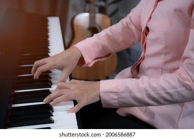 A woman in pink shirt press the key on paino with two hands, playing paino at home, relaxing time with music, music healing, increasing concentration with paino and improving brain concept.