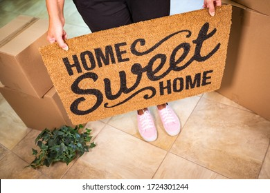 Woman in Pink Shoes Holding Home Sweet Home Welcome Mat, Boxes and Plant.