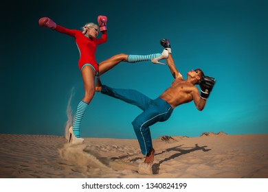 Woman in pink sport suit are fighting with man on sand dunes