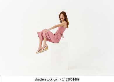 woman in a pink suit sitting