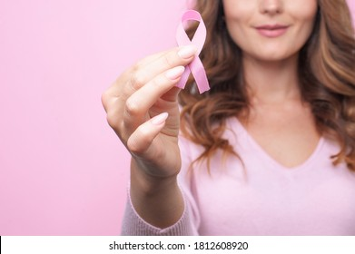 Woman in pink sweater with pink ribbon supporting breast cancer awareness campaign. Breast Cancer Awareness Month
