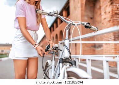 Woman in a pink t-shirt near the fence parking in the summer in the park. Locks, locks the cable with a code number. Protection against hijackings and scammers and thieves. Safety bike in the city.