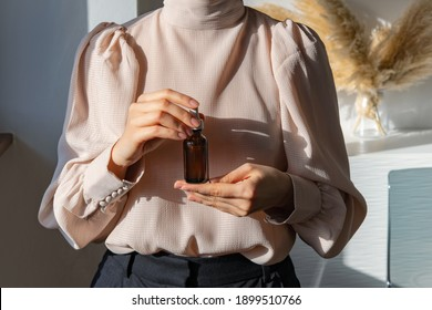 Woman in pink vintage blouse holding serum glass bottle with pipette. Ascorbic Acid, Resveratrol, Caffeine Solution. Hydration of skin and eye contour, trendy colors. Skin care routine concept.  - Shutterstock ID 1899510766
